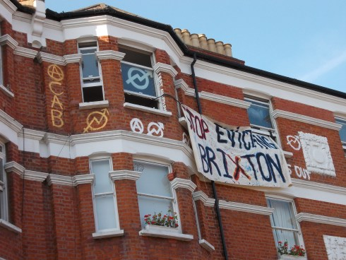 'Stop Evicting Brixton', ACAB, also 'we eat guardians' written down the side of a window